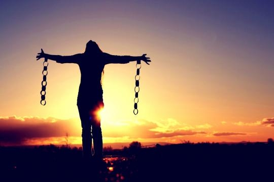 Persona sostiene dos trozos de una cadena con una puesta de sol detrás