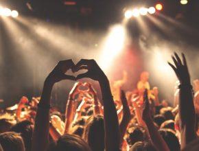 Imagen de un concierto donde unas manos dibujan un corazón