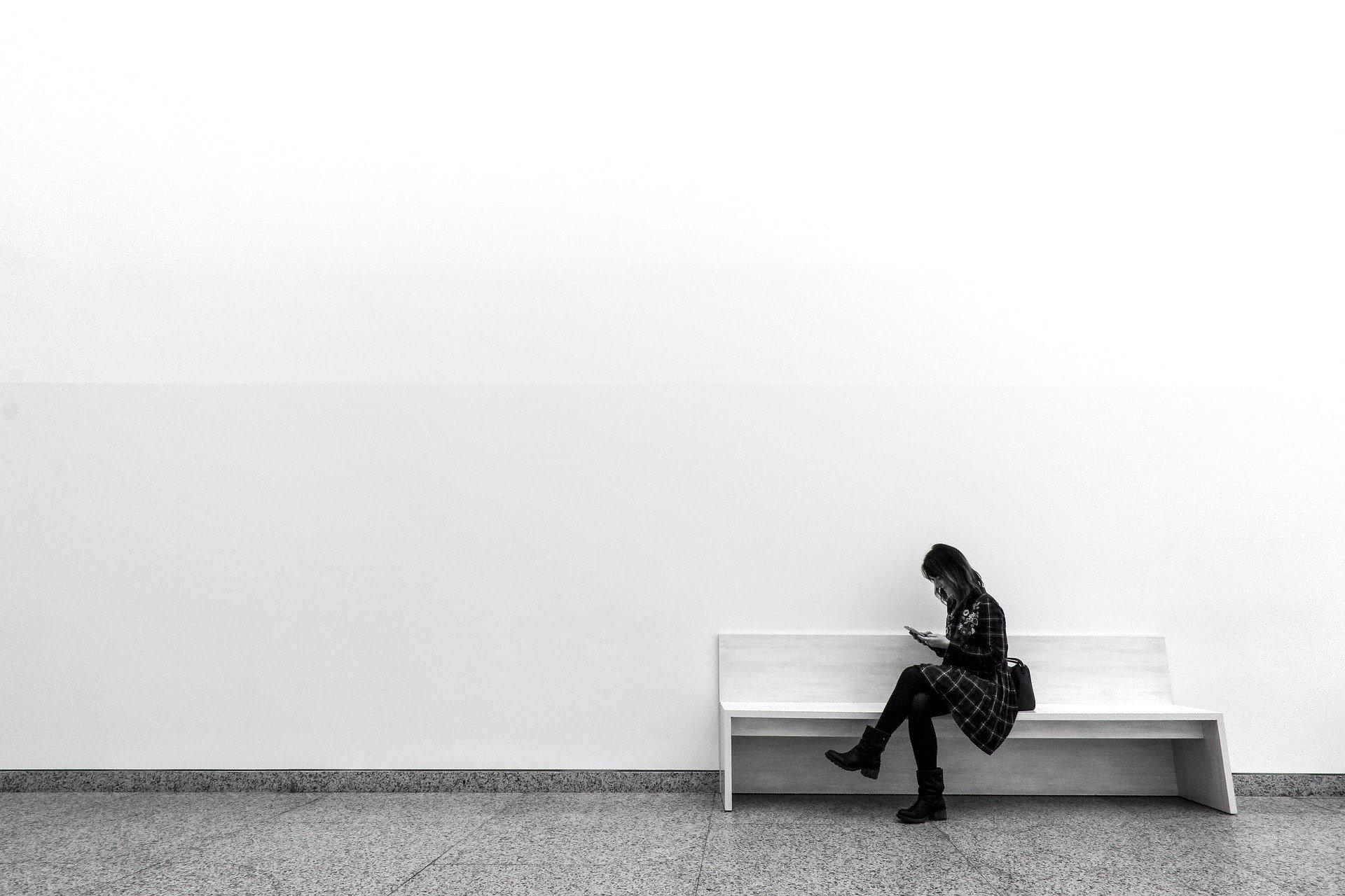 mujer esperando sentada en un banco